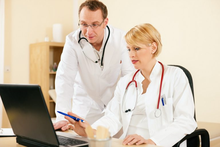 two doctors looking at a monitor