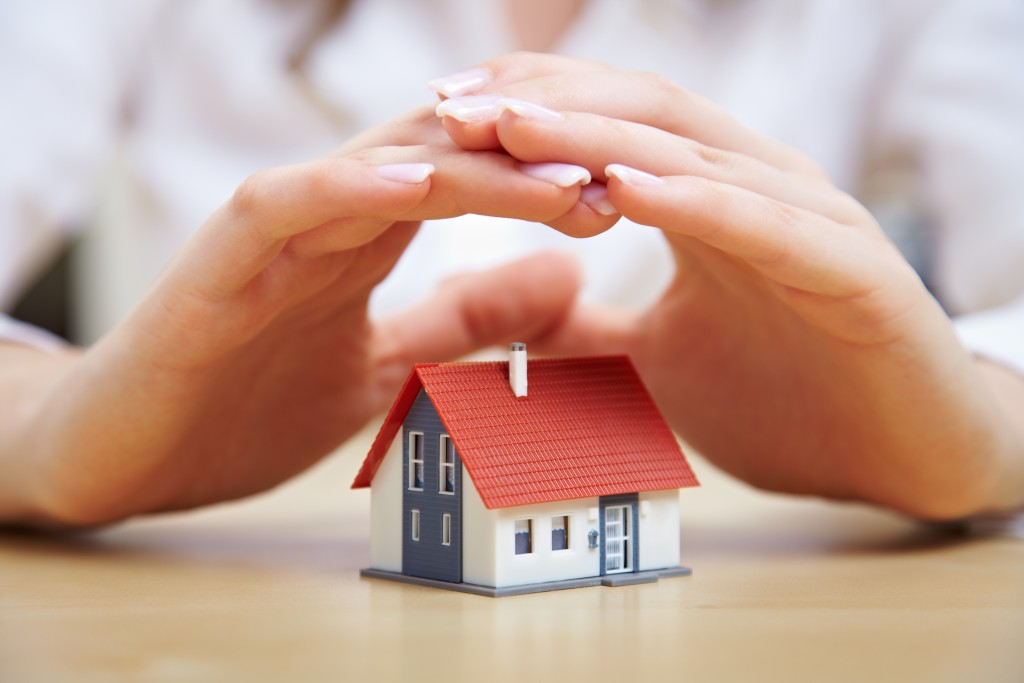 hands covering a miniature home