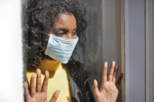 woman looking outside the window wearing facemask due to lockdown