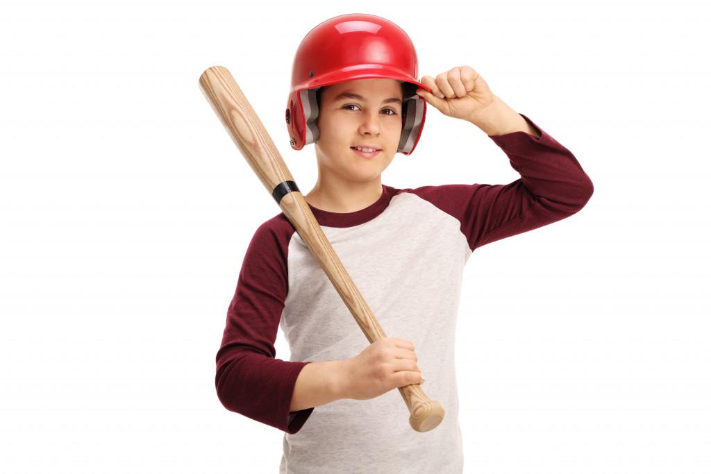 kid wearing a baseball helmet